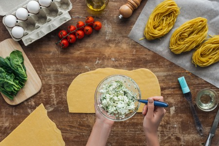 top view of female hands mixing spinach and creamy cheese with spoon in bowl on wooden table Standard-Bild - 112310033