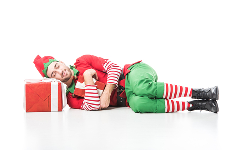 man in christmas elf costume sleeping on pile of presents isolated on white