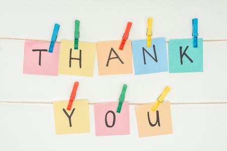 Coloridas notas adhesivas ortografía gracias en encaje con pinzas para la ropa aislado sobre fondo blanco. Foto de archivo