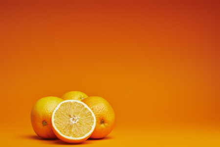 close-up view of fresh ripe whole and sliced oranges on orange background Banco de Imagens