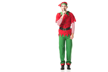 smiling man in christmas elf costume showing hush silence sign and looking at camera isolated on white