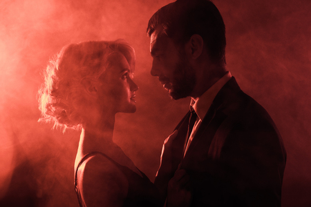 Beautiful couple amorously looking at each other on red smoke background