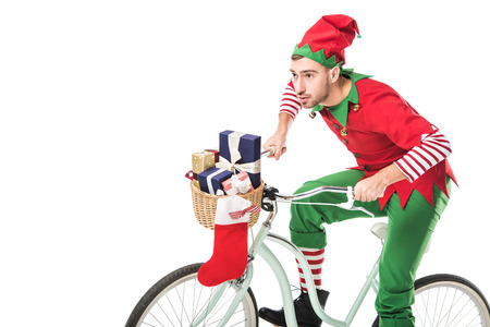 focused man in christmas elf costume riding bike and transporting presents in basket isolated on white