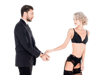 Attractive woman in lingerie touching man hands in handcuffs isolated on white Stock Photo