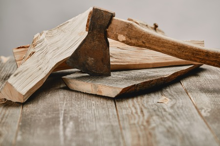 Close up view of axe and wood logs on wooden table on grey background