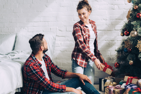 happy young woman putting gift box under christmas tree and talking to boyfriend in bedroom at home