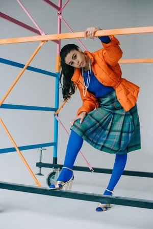stylish girl in orange winter jacket, checkered skirt and blue tights posing near colorful scaffold in studio Imagens