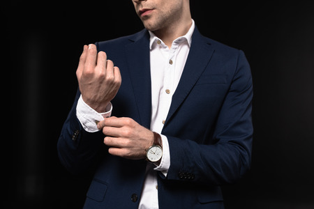 cropped shot of young businessman buttoning cuffs on sleeve isolated on black