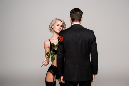 Seductive woman in lingeriewith red rose near man in black costume isolated on grey Standard-Bild - 112355434