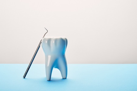 close up view of tooth model and dental probe on blue and white background Stock Photo