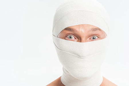 close up of man face covered with white bandages after plastic surgery isolated on white Imagens