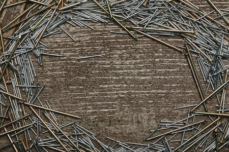 Top view of cooper and silver-colored nails arranged on wooden table