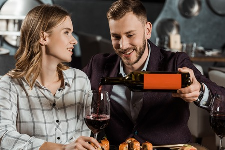 Attractive smiling couple having dinner and man pouring wine in glass in restaurant Imagens