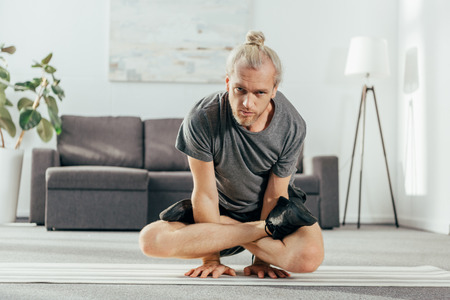 adult man balancing on arms with crossed legs and looking at camera while training at home