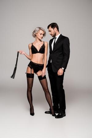 Atractiva pareja de mujer adulta joven en lencería con látigo y hombre guapo en traje aislado en gris