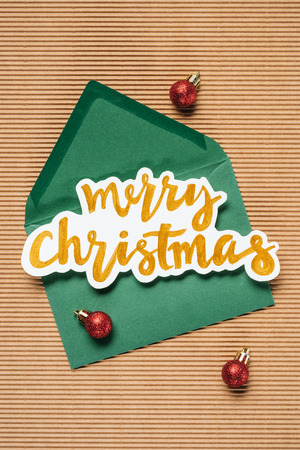 Flat lay of green envelope with Merry Christmas sign and red Christmas balls on the textured background