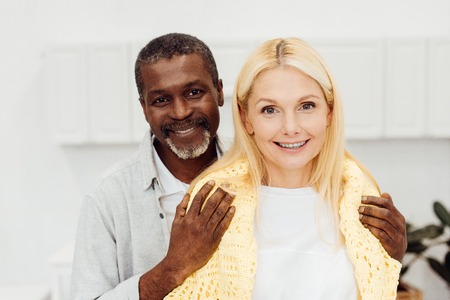 happy african american man embracing smiling blonde woman