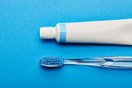 top view of toothbrush and toothpaste arranged on blue backdrop, dentistry concept