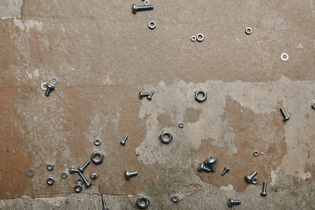 Top view of screws and bolts scattered on the background of old  surface Stock Photo