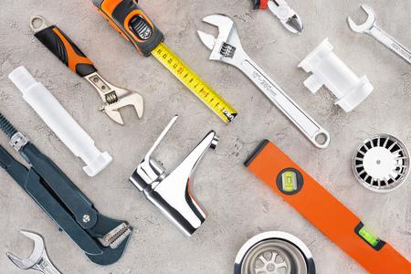 Lay Flat con diversas herramientas de fontanería sobre superficie de hormigón Foto de archivo