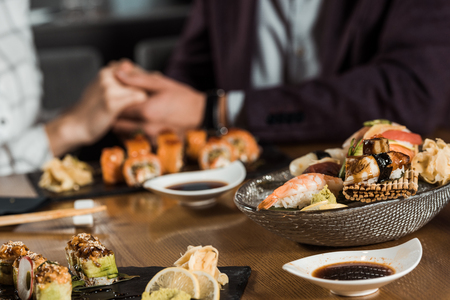 Sushi rolls and seafood on the background of couple holding hands Imagens