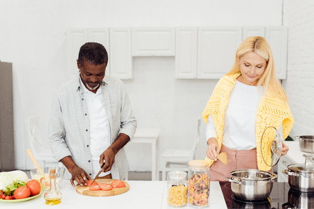 african american man and mature woman preparing dinner together
