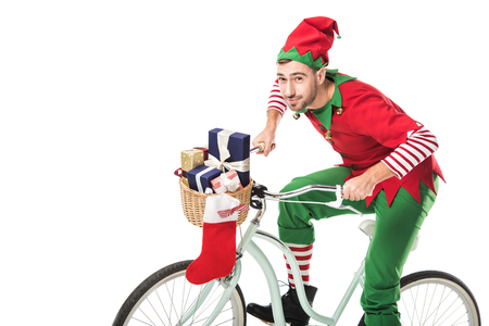 smiling man in christmas elf costume riding bike and transporting presents in basket isolated on white background