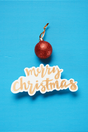 Flat lay of Merry Christmas sign and christmas ball on the blue textured background
