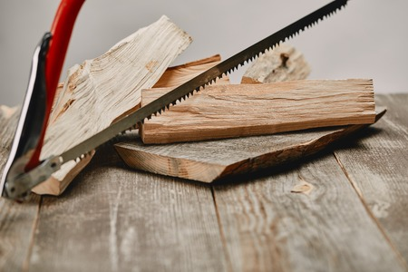 Close up view of hacksaw and wood logs on wooden table on grey background Stock Photo