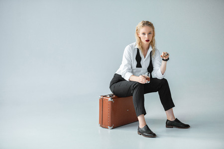 fashionable girl holding glass of whiskey and smoking cigar while sitting on retro suitcase on grey 스톡 콘텐츠