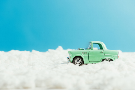side view of toy car riding by snow made of cotton on blue background