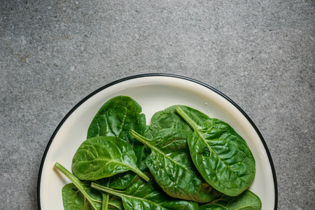 Top view of wet fresh spinach leaves on plate