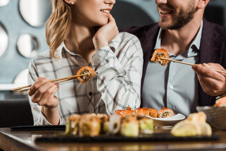 Cropped view of smiling happy couple eating sushi in restaurant Stockfoto