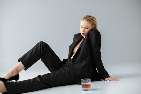 attractive fashionable girl in black trendy suit sitting on grey with glass of cognac