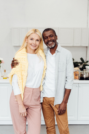 african american man embracing blonde mature woman at kitchen