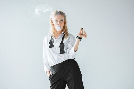 attractive stylish blonde girl smoking cigar isolated on grey