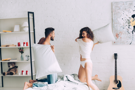happy young couple having fun and fighting by pillows in bedroom at home Stock Photo