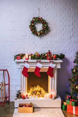 Fireplace with decorations near Christmas tree at home