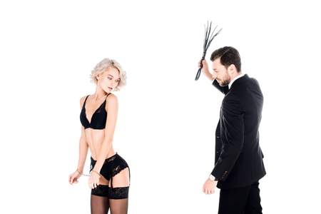 Verführerische schöne Frau, die in wundervollen Dessous steht, während der Mann seine Hand mit der Peitsche einzeln auf Weiß hebt