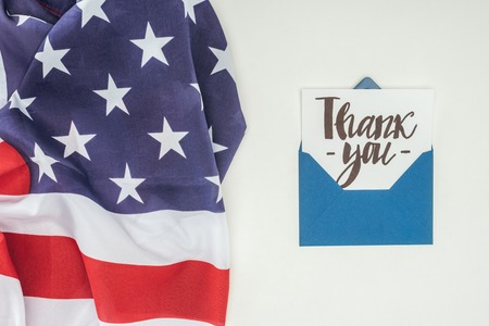 thank you lettering sticking out of blue envelope with american flag isolated on white background