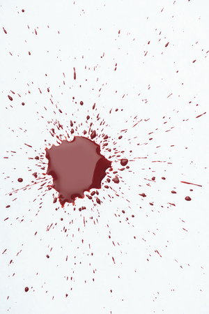 top view of messy blood splash with small droplets on white surface