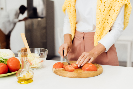 cropped view of woman slicing tomatoes on chopping board 版權商用圖片