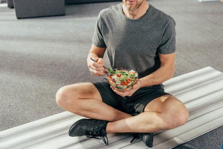 colpo ritagliato di un uomo atletico in abbigliamento sportivo seduto su un tappetino da yoga e che tiene in mano una ciotola con insalata di verdure a casa