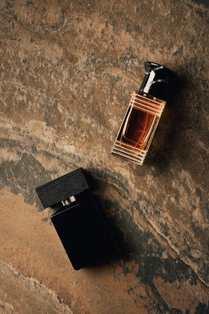 top view of bottles of perfumes on brown weathered surface