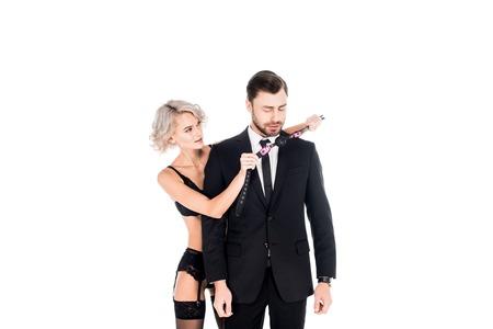 Attraente giovane donna adulta che mostra bavaglio all'uomo in costume nero isolato su bianco