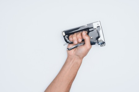 cropped shot of man holding stapler isolated on white