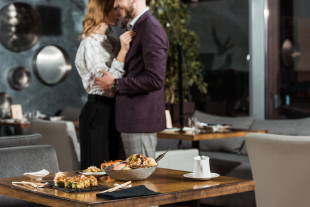 Partial view of beautiful hugging couple dancing behind the table served with sushi in restaurant Imagens