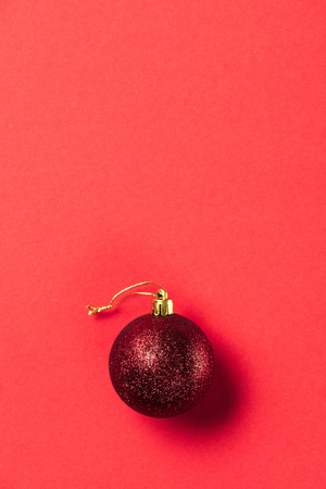 top view of red shiny decorative christmas ball on red background