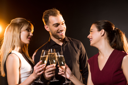 group of happy friends clinking champagne glasses under golden light on black