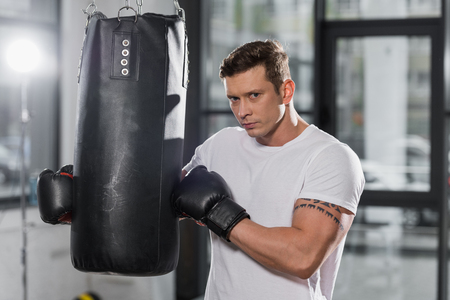 handsome muscular boxer holding punching bag and looking at camera in gym 版權商用圖片